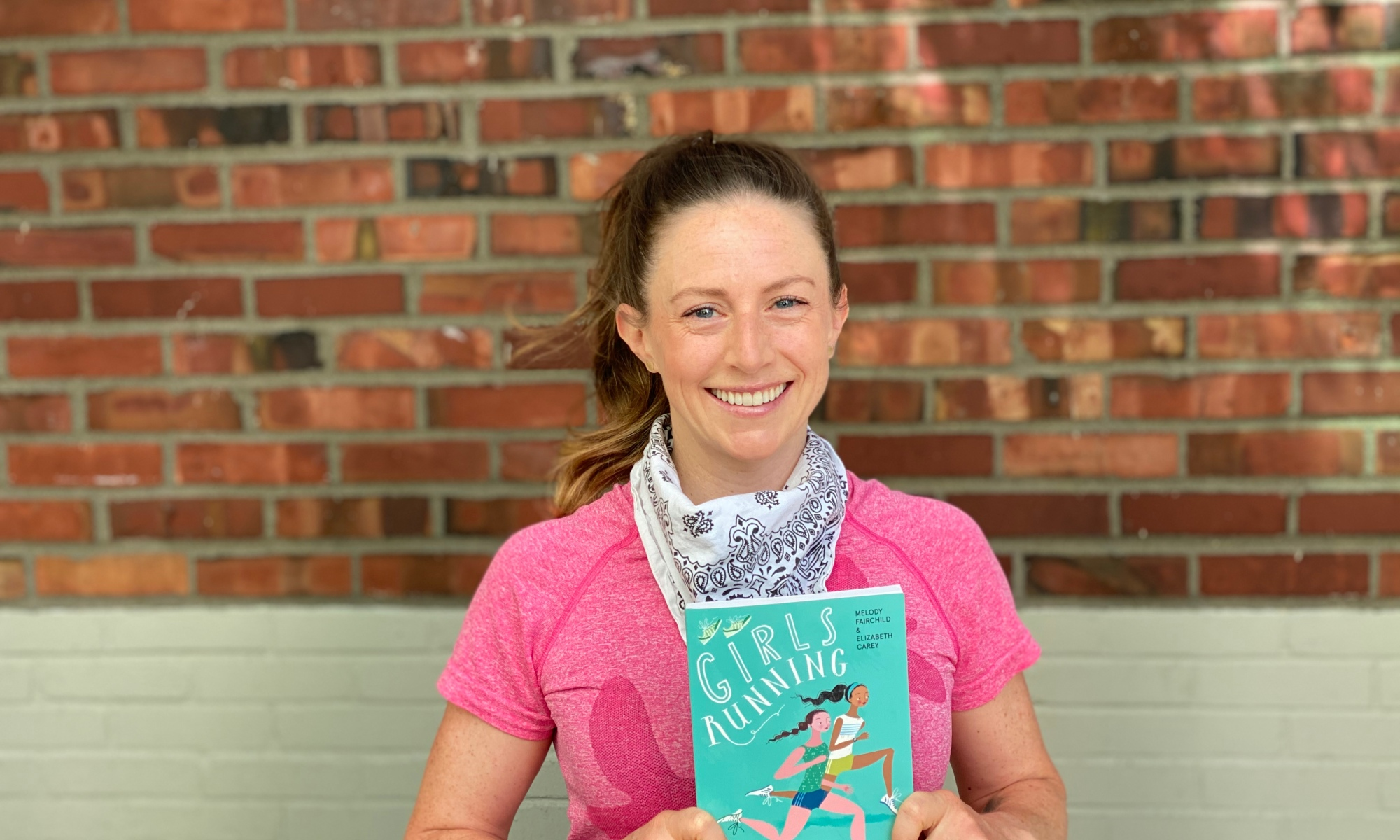 Author Elizabeth Carey holds her book Girls Running: All You Need To Strive, Thrive, and Run Your Best, co-authored with Melody Fairchild